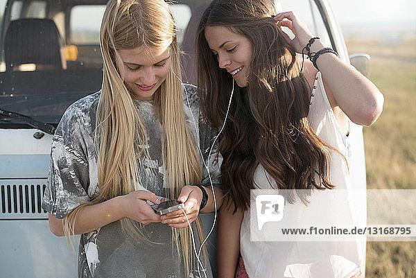 Zwei junge Frauen hören Musik auf einem mp3-Player
