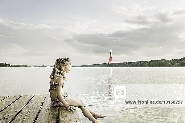 Bikinitragendes Mädchen am Seepier sitzend  München  Bayern  Deutschland