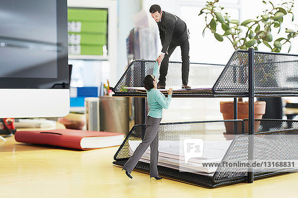 Businessman offering helping hand to colleague on large inbox on oversized desk