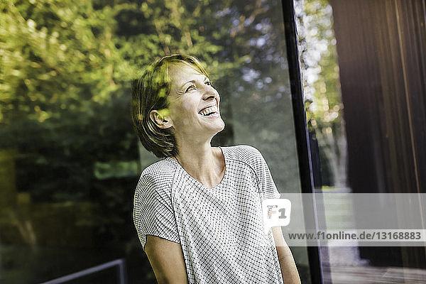 Porträt einer reifen Frau  die vom neuen Haus aufschaut