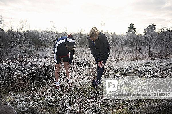 Mutter und Sohn auf frostigem Grasland  die Hände auf den Knien die Beine ausgestreckt und nach unten blickend