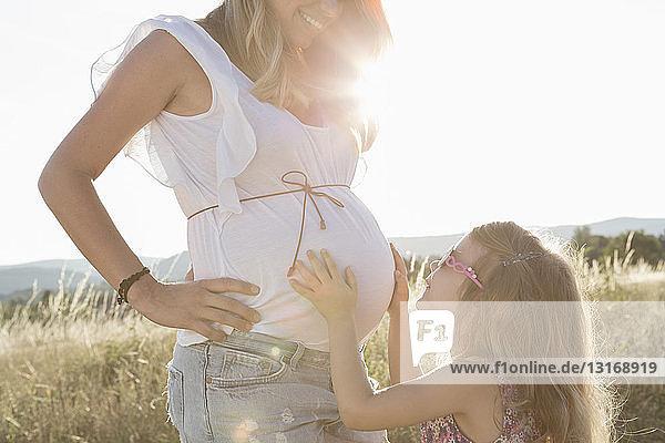 Mädchen berührt auf dem Feld schwangeren Bauch von Müttern