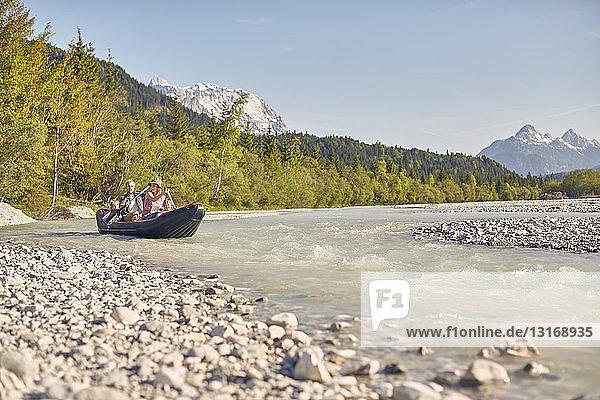 Familie benutzt Paddel zum Steuern eines Schlauchbootes auf dem Wasser  Wallgau  Bayern  Deutschland