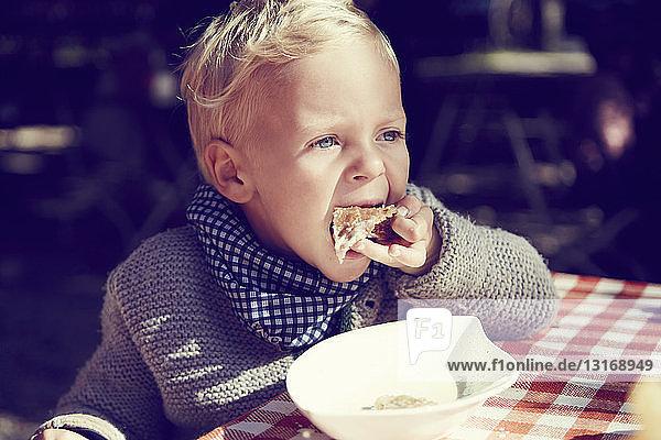 Süßer Junge isst Toast in der Küche