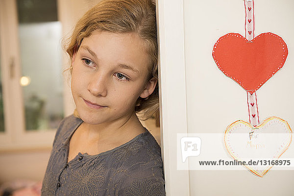 Portrait of girl leaning against bedroom wall and gazing