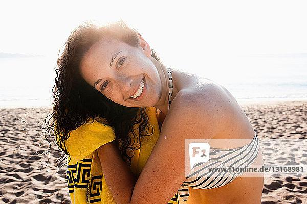 Frau trocknet ihr Haar am Strand