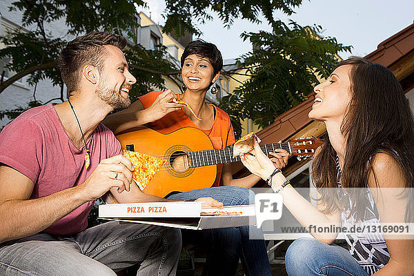 Three friends eating pizza  woman playing guitar