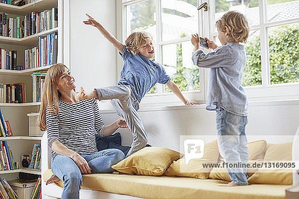 Junger Junge fotografiert Mutter und Bruder mit einem Smartphone
