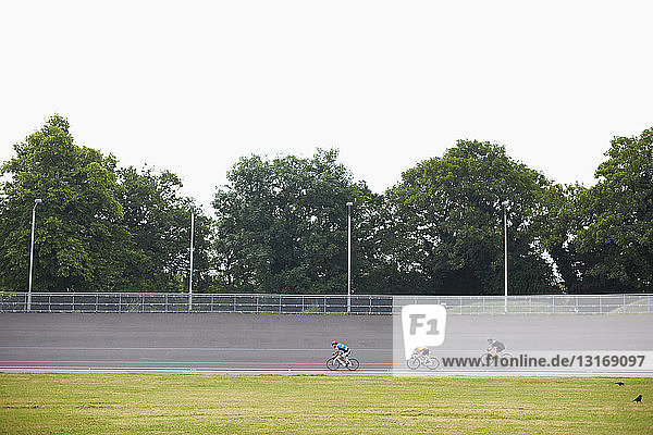 Three cyclists cycling on track at velodrome  outdoors