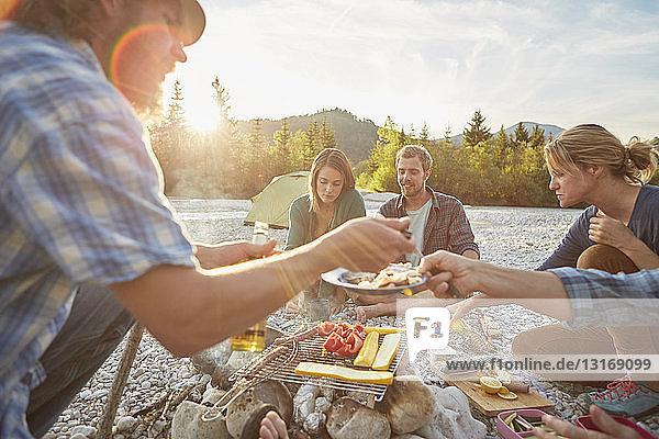 Erwachsene sitzen am Lagerfeuer und servieren Essen vom Grill