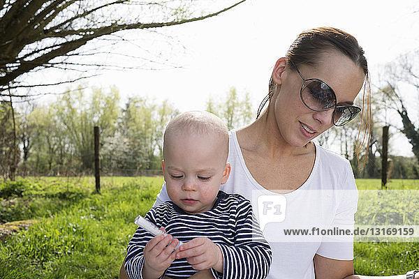 Baby boy sitting on mothers lap in field