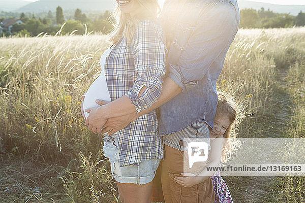 Ein schwangeres junges Paar und eine Tochter  die sich auf dem Feld umarmen