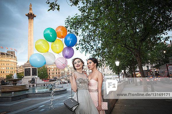 Zwei junge Freundinnen in Abendkleidern posieren mit Luftballons  Trafalgar Square  London  UK