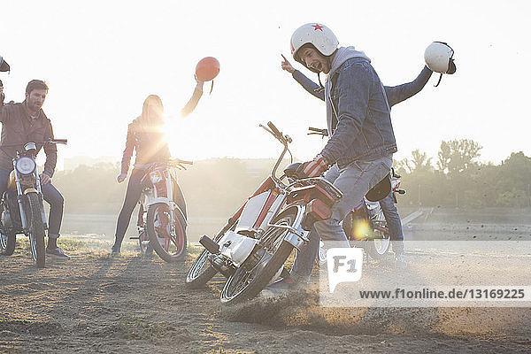Kleine Gruppe von Freunden sitzt auf Mopeds und hält Sturzhelme in der Luft