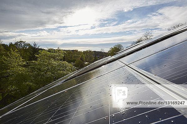 Erhöhte Nahaufnahme der sonnenbeschienenen Sonnenkollektoren auf dem Hausdach