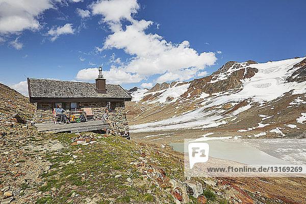 Junges Wanderpaar macht Rast vor der Hütte  Schnalstaler Gletscher  Schnalstalstal  Südtirol  Italien