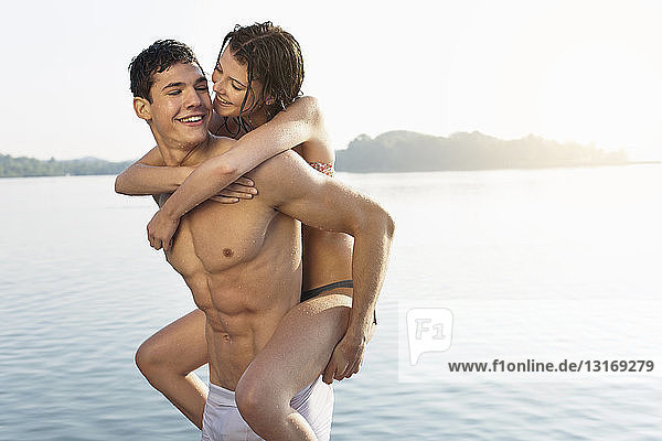 Young man giving girlfriend piggyback