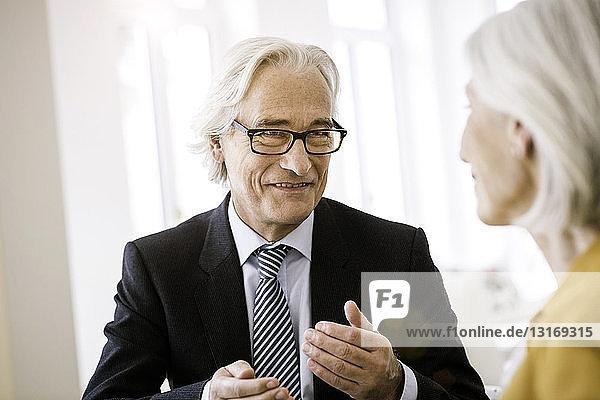 Älterer Mann in Hemd  Krawatte und Anzugjacke im Gespräch mit älterer Frau