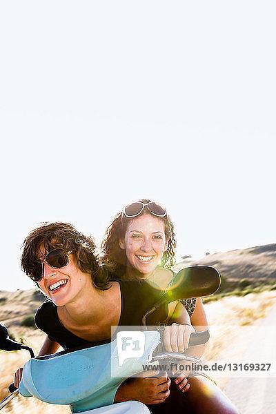Lächelnde Frauen  die zusammen Roller fahren