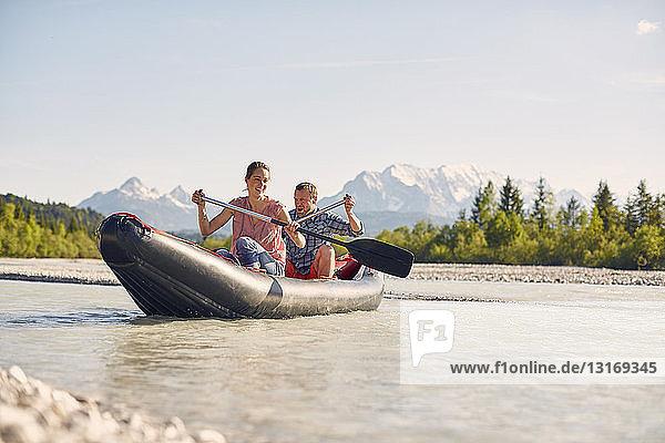 Ehepaar mit Paddel zum Steuern eines Beibootes auf dem Wasser  Wallgau  Bayern  Deutschland