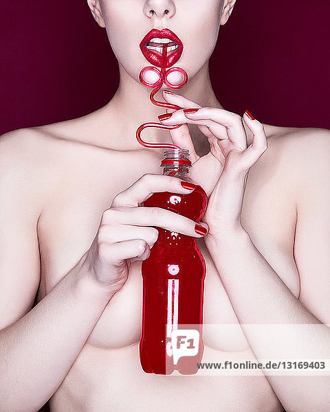 Frau trinkt rote Soda mit gelocktem Strohhalm