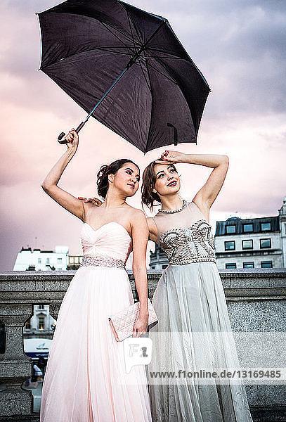 Porträt zweier weiblicher Models  die mit Regenschirm posieren  Trafalgar Square  London  UK