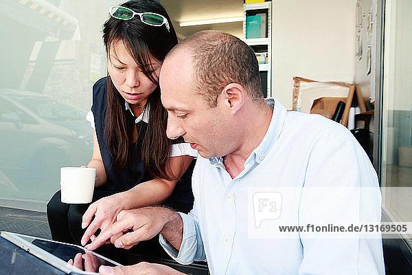 Männliche und weibliche Architekten betrachten das digitale Tablet im Büro