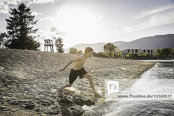 Teenager rennt am Strand zum Wasserrand  Sand Point  Idaho  USA