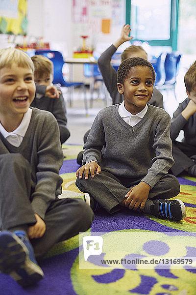 Children sitting crosslegged on floor in elementary school classroom