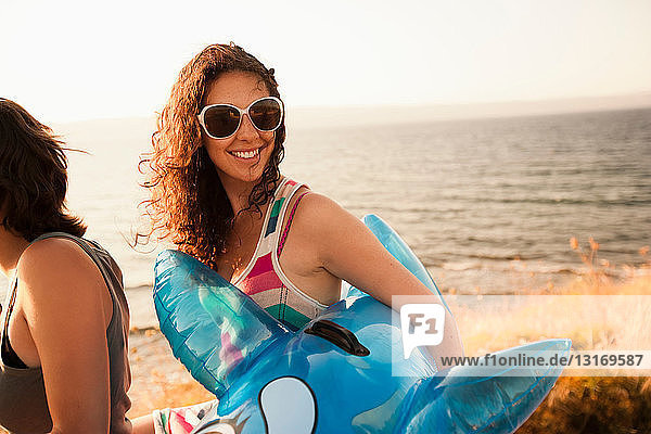 Frau trägt aufblasbares Spielzeug am Strand
