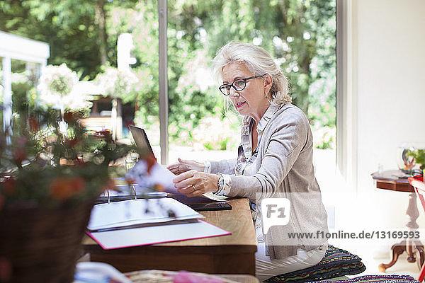 Ältere Frau am Tisch sitzend  Papierkram durchsehen  Laptop benutzen
