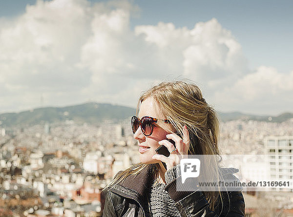 Female tourist talking on smartphone in front of cityscape from Montjuic Hill  Barcelona  Spain