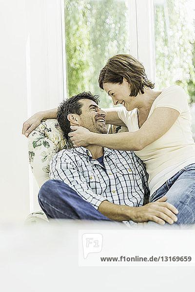 Romantisches reifes Paar sitzt auf einem Sessel im Wohnzimmer