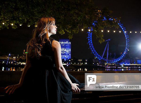 Junge Frau starrt nachts auf das London Eye  London  UK