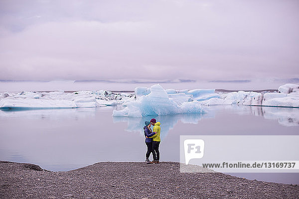 Side view of mid adult couple face to face hugging by Jokulsarlon glacial lake  Iceland