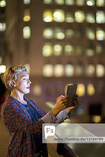Mature woman using digital tablet in front of office at night  London  UK