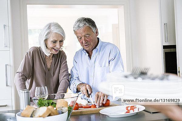 Älteres Ehepaar bereitet das Mittagessen an der Küchentheke vor