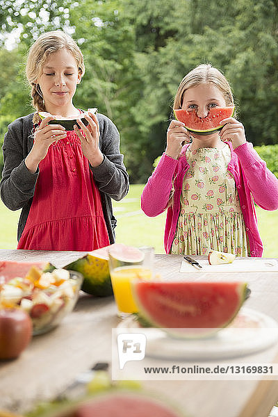Two sisters at patio table eating and holding up watermelon slice