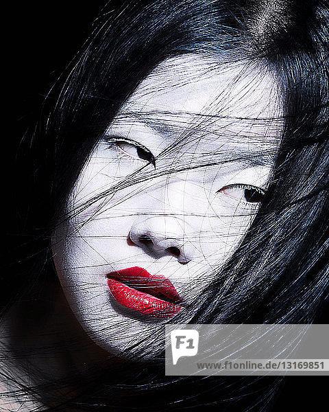 Junge Frau mit dramatischem Make-up  weißem Gesicht und rotem Lippenstift