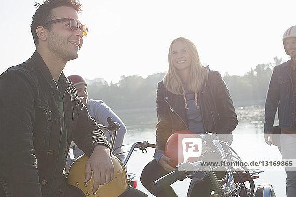 Gruppe von Freunden sitzt auf einem Moped am See
