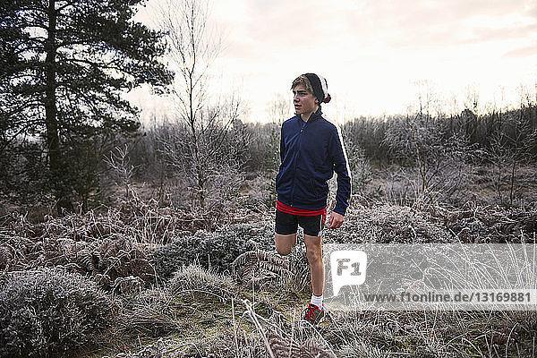 Teenager Junge auf frostigem Grasland in Sportkleidung  der das Bein streckt und wegschaut