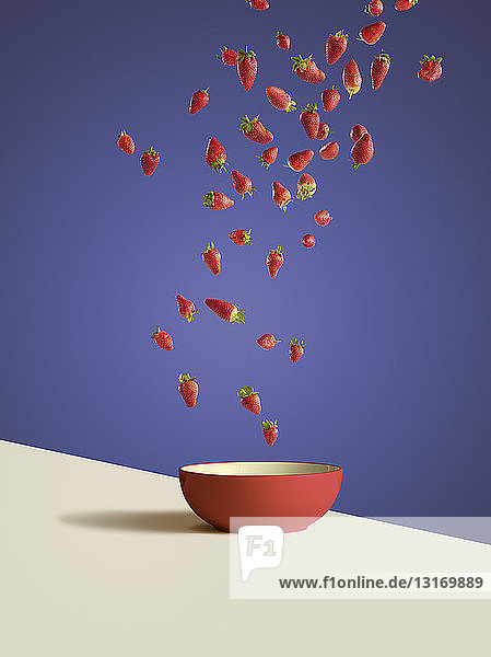 Fresh sliced strawberries dropping into red bowl