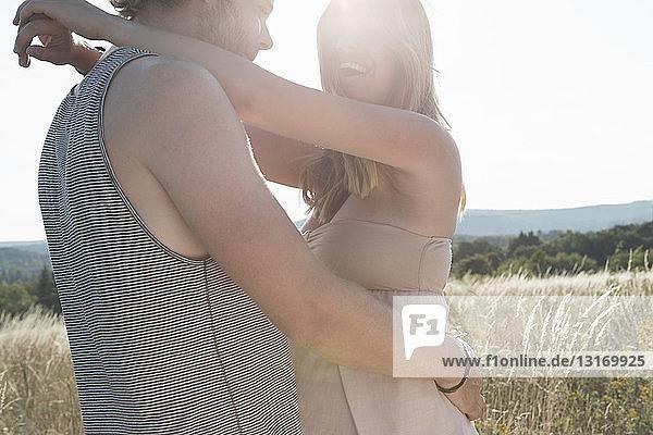 Schwangere junge Frau und ihr Freund umarmen sich auf dem Feld