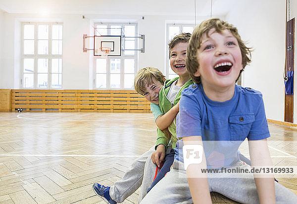 Jungen sitzen auf einer Bank in der Schulhalle und lachen
