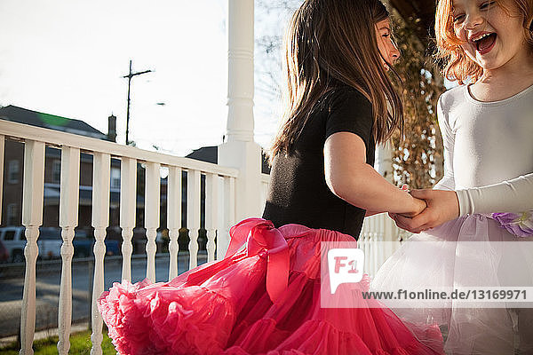Girls dancing in ballet costumes on porch