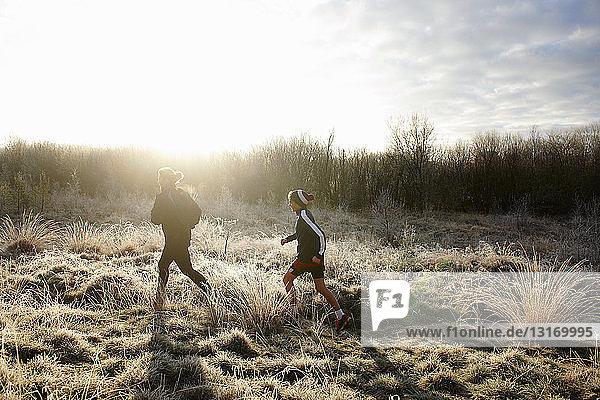 Seitenansicht von Mutter und Sohn beim Laufen auf Grasland