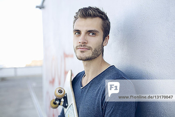 Porträt eines jungen Mannes  der ein Skateboard hält und wegschaut