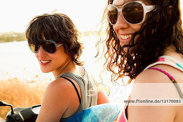 Lächelnde Frauen fahren Roller am Strand