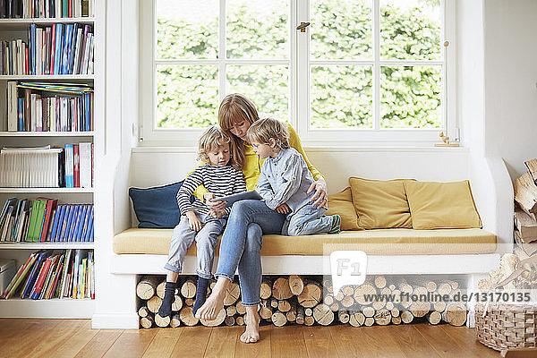 Mutter und zwei Söhne sitzen auf einem Fensterplatz und schauen auf ein digitales Tablett