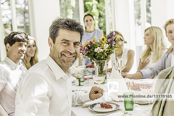 Portrait of mature man at family birthday party table